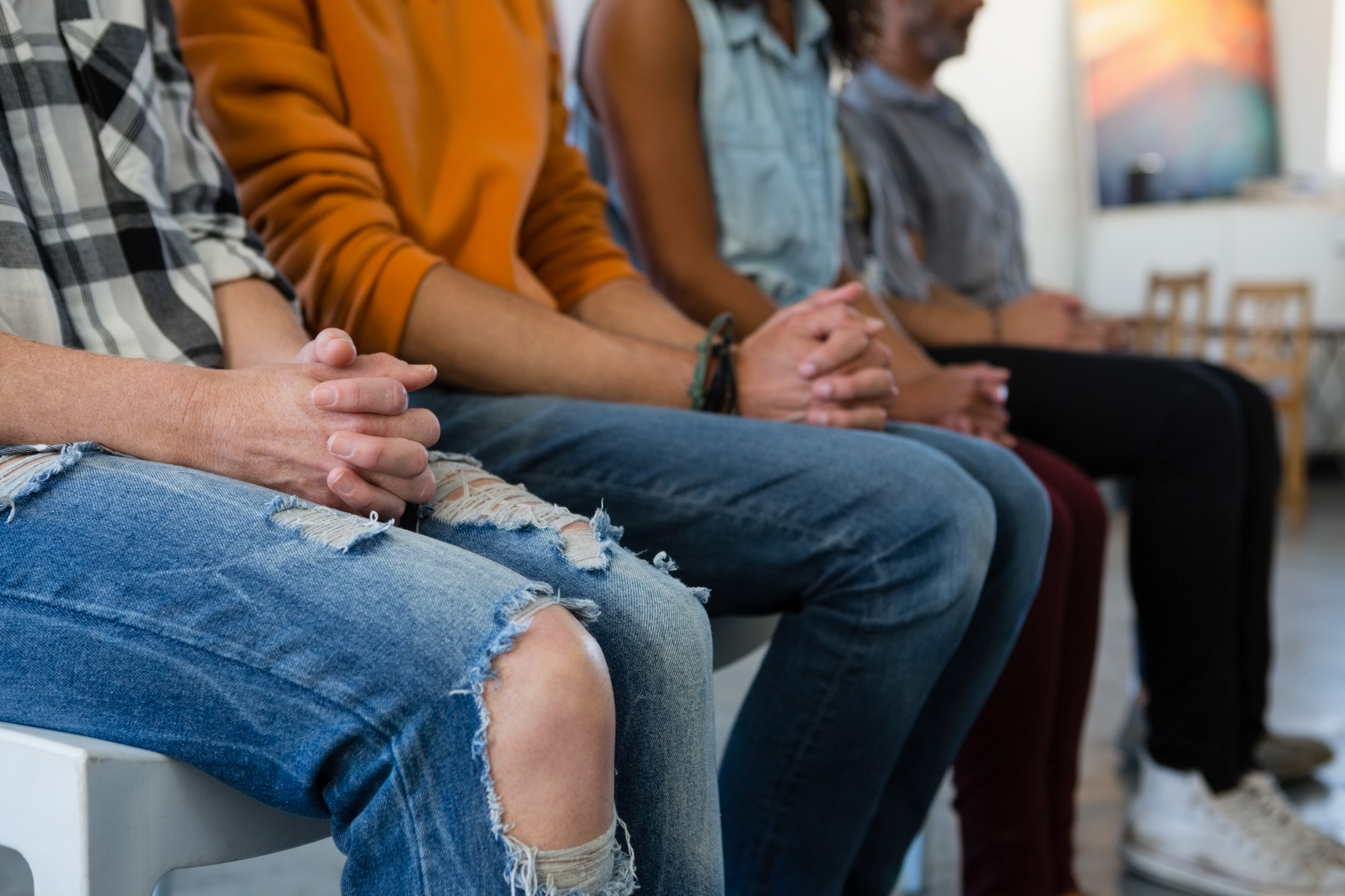 Adult students with hands clasped sitting on chair
