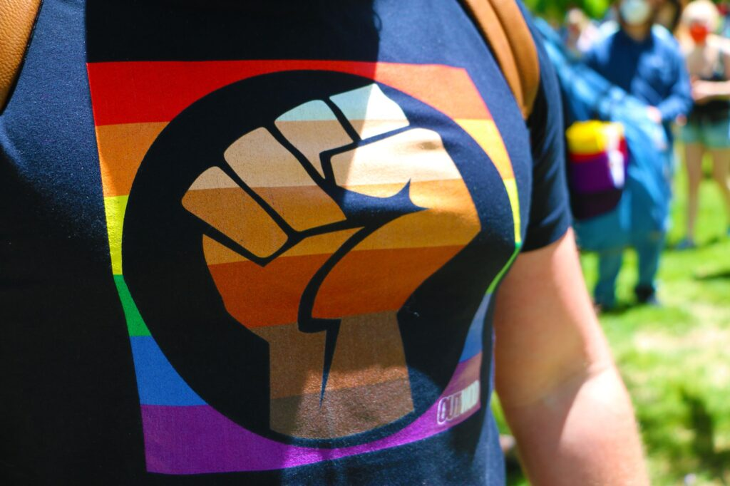 Black Power fist on gay pride t-shirt.